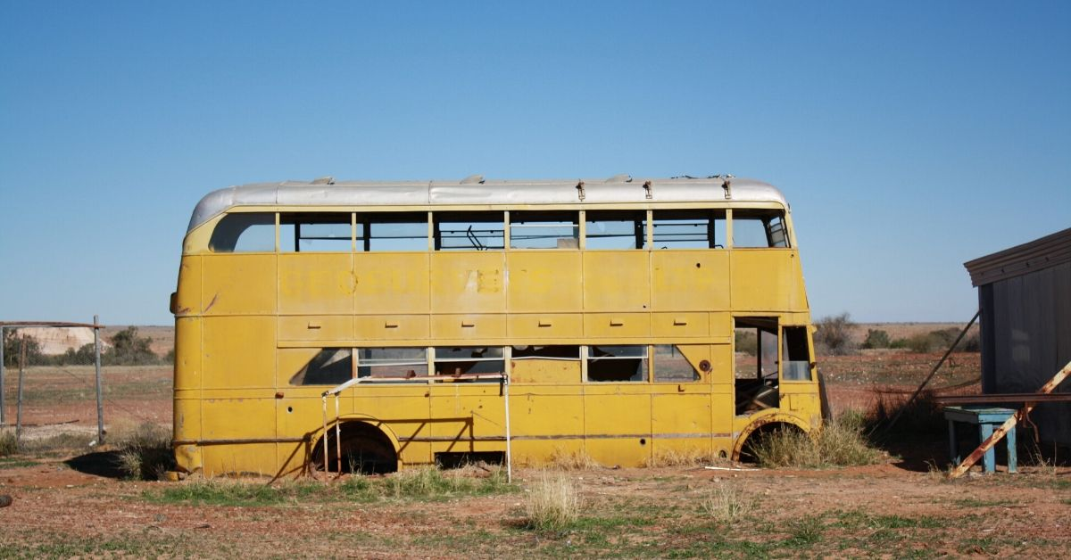 rusty yellow bus against outback sky