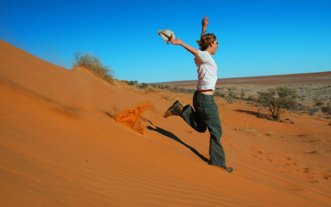 girl running down a red sand dune with arms in the air