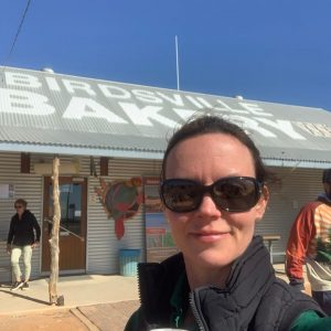 Amy Annetts at Birdsville bakery holding a coffee